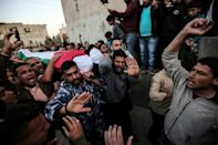 Mourners carry the body of a Palestinian killed during clashes with Israeli forces on the Israeli-Gaza border, during his funeral in the Gaza Strip on April 6, 2018
