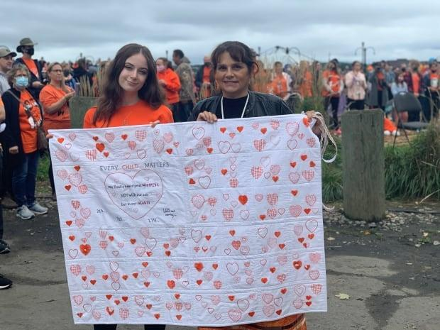 Cheyenne Hardy (right) and Pamela Glode-Desrochers hold up a quilt donated to the Mi'kmaw Native Friendship Centre in Halifax. The blanket, designed by Hardy, commemorates the unmarked graves found on the grounds of former residential schools in Canada. (Taryn Grant/CBC - image credit)