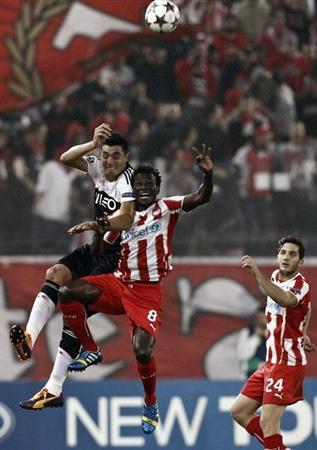 Olympiakos' N'Dinga jumps for the ball against Benfica's Cardozo during their Champions League soccer match in Piraeus near Athens
