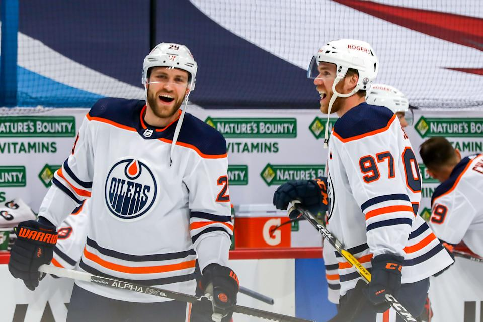 WINNIPEG, MB - APRIL 26: Leon Draisaitl #29 and Connor McDavid #97 of the Edmonton Oilers share a laugh during the pre-game warm up prior to NHL action against the Winnipeg Jets at the Bell MTS Place on April 26, 2021 in Winnipeg, Manitoba, Canada. (Photo by Jonathan Kozub/NHLI via Getty Images)