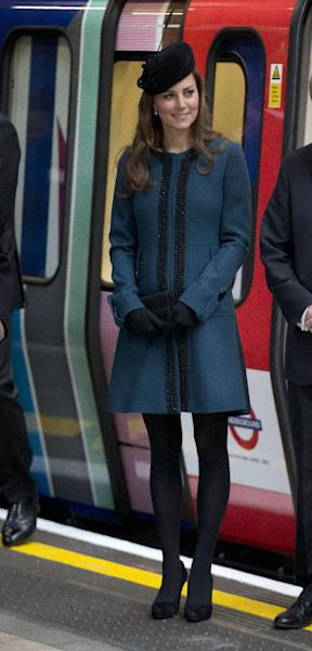 FILE - This March 20, 2013 file photo shows Kate, the Duchess of Cambridge, pregnant with her first child, watching as Queen Elizabeth II unveils a plaque at Baker Street underground station in London, during a visit to mark the 150th anniversary of the London Underground, The Duchess of Cambridge, Kate Middleton, possesses what might be the world's most famous baby bump, and she has made a seamless transition into her slightly revamped look. Fashion experts say streamlined style best suits a baby bump. (AP Photo/Matt Dunham, file)