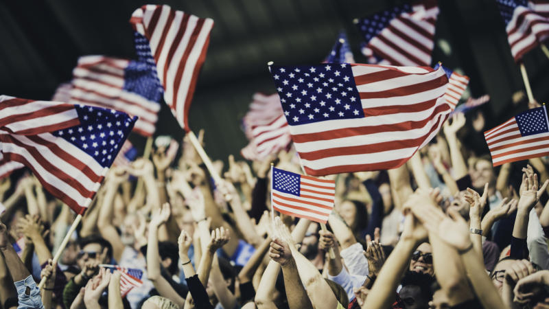 People with USA flags on a stadium cheering for their team during a sports event.
