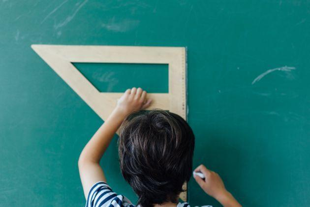 Close up of boy using wooden ruler on blackboard. (Photo: MANICO via Getty Images)