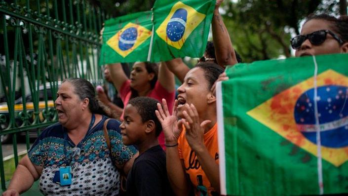Relatives and friends of Evaldo dos Santos Rosa protest in Rio de Janeiro with red-stained Brazilian flags