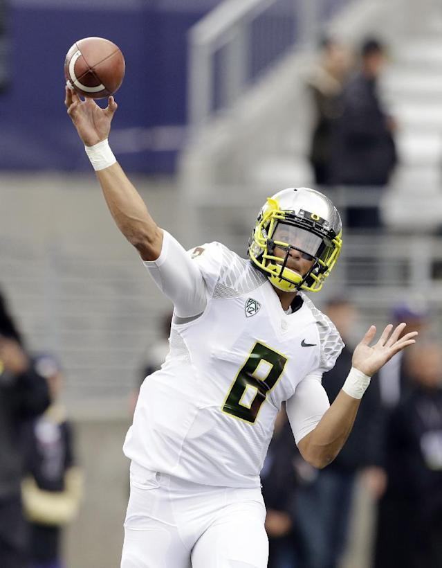 Oregon quarterback Marcus Mariota warms up before an NCAA college football game against Washington, Saturday, Oct. 12, 2013, in Seattle. (AP Photo/Elaine Thompson)