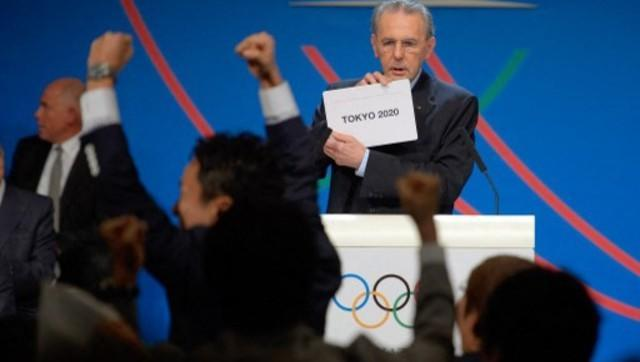 This file photo taken on 7 September, 2013 shows then-IOC president Jacques Rogge displaying the name of Tokyo as it is elected to host Olympics. AFP/File