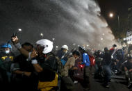 Police use water cannons to disperse pro-democracy protesters during a street march in Bangkok, Thailand Sunday, Nov. 8, 2020. The protesters continue to gather Sunday, led by their three main demands of Prime Minister Prayuth Chan-ocha's resignation, changes to a constitution that was drafted under military rule and reforms to the constitutional monarchy. (AP Photo/Sakchai Lalit)