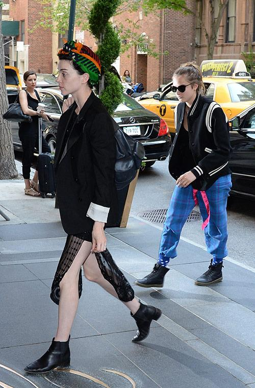 The pair looked a bit mismatched walking in NYC, with Clark sporting a chic, tribal-print headwrap, boyfriend blazer, and Chelsea boots, and Delevingne in a varsity jacket and comfy plaid pants, tucked into her socks.