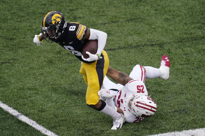 Iowa wide receiver Ihmir Smith-Marsette (6) is tackled by Wisconsin safety Eric Burrell (25) during the first half of an NCAA college football game, Saturday, Dec. 12, 2020, in Iowa City, Iowa. (AP Photo/Charlie Neibergall)