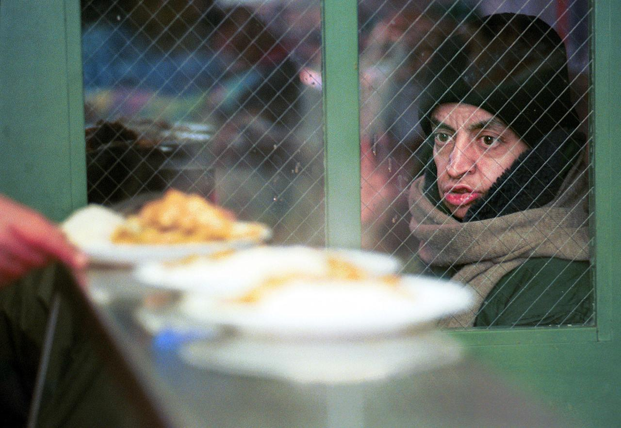<p>A homeless woman eyes hot meals lined up in the soup kitchen of Trinity Lutheran Parish church December 28, 2000 before a lunchtime meal in New York City. Trinity Church runs a program called Shelter and Food for the Homeless, which serves a daily meal to homeless people in the area. (Photo by Chris Hondros/Newsmakers) </p>