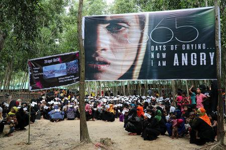 Banners are seen as Rohingya refugee women take part in a protest at the Kutupalong refugee camp to mark the one year anniversary of their exodus in Cox's Bazar