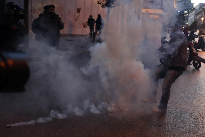 A protester kicks back a tear gas canister toward the riot police, during a protest near Parliament Square, In Beirut, Lebanon, Saturday, March. 13, 2021. Riot police fired tear gas to disperse scores of people who protested near parliament building in central Beirut Saturday amid deteriorating economic and financial conditions and as the local currency hit new low levels. (AP Photo/Bilal Hussein)