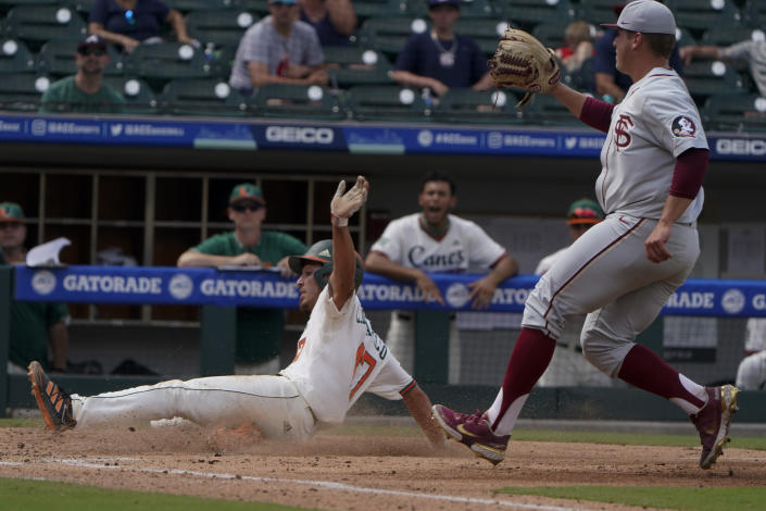 Miami's Christian Del Castillo scores past Florida State pitcher Parker Messick on a wild pitch in the second inning of an NCAA college baseball game at the Atlantic Coast Conference tournament on Friday, May 28, 2021, in Charlotte, N.C. (AP Photo/Chris Carlson)
