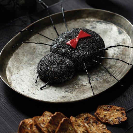 """<p>Sautéed shallots and feta cheese flavor this simple spread, which is a delicious hors d'oeuvre at any time of year. Here, it's formed into a spooky spider.</p><p><a href=""""https://www.foodandwine.com/recipes/black-widow-goat-cheese-log"""">GO TO RECIPE</a></p>"""