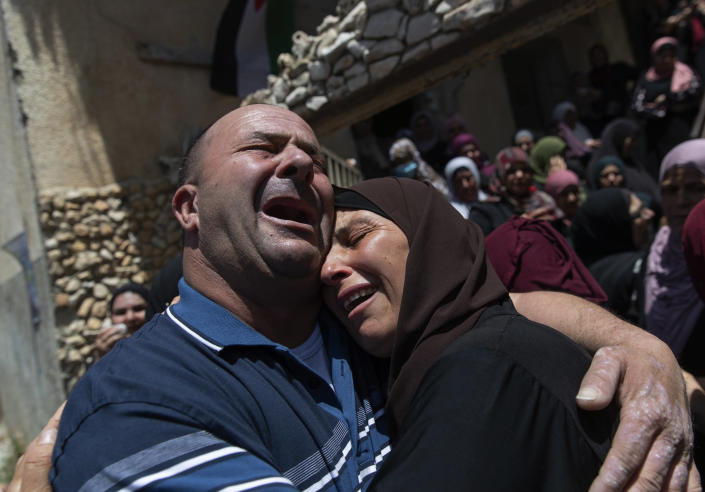 Palestinian mourners cry while taking a last look at the body of Mohammad Daraghmeh at the family house during his funeral in the West Bank village of Lubban, near Nablus, Wednesday, May 12, 2021. Israeli soldiers opened fire yesterday at a Palestinian vehicle at an army checkpoint north of the West Bank, killing Daraghmeh, a passenger, and critically wounding another, the Palestinian health ministry said. (AP Photo/Nasser Nasser)