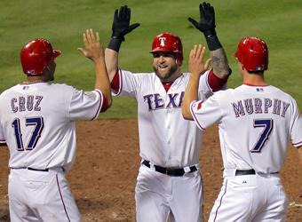 Mike Napoli is greeted by Rangers teammates Nelson Cruz and David Murphy after his three-run homer in Game 4