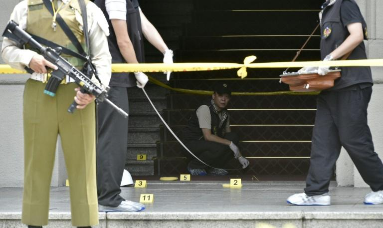 An armed military policeman keeps watch as investigators collect evidence at the scene where a samurai sword-wielding attacker slashed a police guard at the Presidential Palace