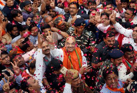 Amit Shah (C), president of ruling Bharatiya Janata Party (BJP) gestures as he celebrates with party supporters after learning of the initial poll results inside the party headquarters in New Delhi, March 11, 2017. REUTERS/Adnan Abidi
