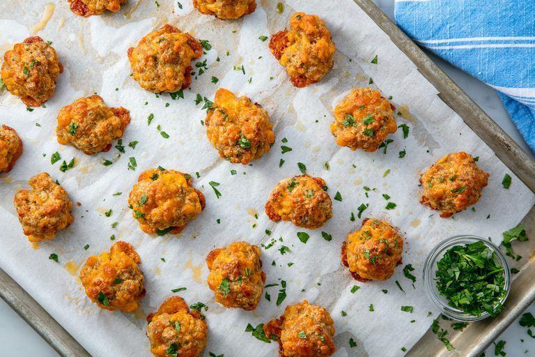 """<p>Sausage balls are a great party buffet dish that might make you go """"Wait, what even is a sausage ball?!"""" The answer: Addictive bites of cooked pork sausage, cheddar, and pre-made pancake mix that will be the most popular canapé at your party.</p><p>Get the <a href=""""https://www.delish.com/uk/cooking/recipes/a30208210/sausage-balls-recipe/"""" rel=""""nofollow noopener"""" target=""""_blank"""" data-ylk=""""slk:Sausage Balls"""" class=""""link rapid-noclick-resp"""">Sausage Balls</a> recipe.</p>"""
