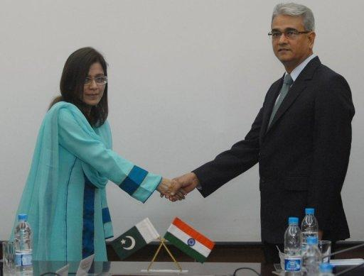 Indian defence official Shashikant Sharama (right) shakes hands with his Pakistani counterpart Nargis Saithi