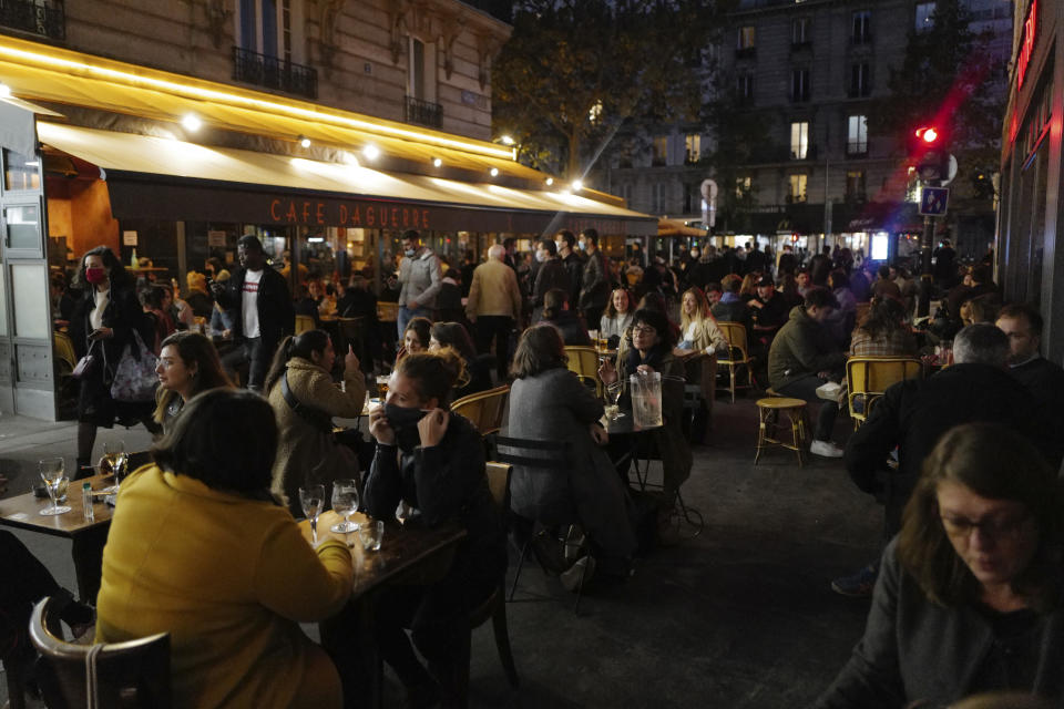 Parisians take a drink on the terrace of a restaurant before the nightly curfew due to the restrictions against the spread of coronavirus, in Paris, France, Friday, Oct. 23, 2020. (AP Photo/Francois Mori)