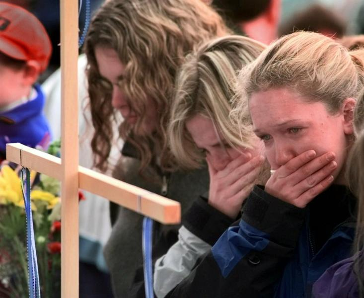 FILE - In this April 22, 1999, file photo, Columbine High School students, from left, Darcy Craig, Molly Byrne and Emily Dubin stop to pay their respects at a makeshift memorial set up in a park near the high school in Littleton, Colo. On April 20, 1999, two teenage gunmen went on a killing rampage at Columbine High School in suburban Denver. (AP Photo/Eric Gay, File)
