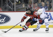 New Jersey Devils center Blake Coleman (20) controls the puck as he is checked by Toronto Maple Leafs defenseman Morgan Rielly (44) during the second period of an NHL hockey game Friday, Dec. 27, 2019, in Newark, N.J. (AP Photo/Bill Kostroun)