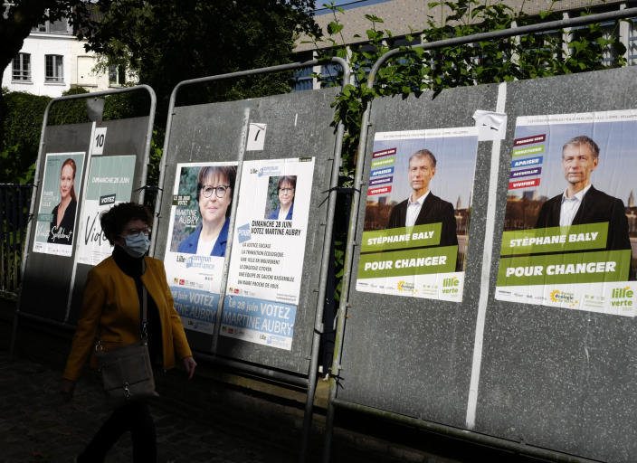 A woman walks past posters advertising the upcoming local election candidates in Lille Sunday, June 28, 2020 in Lille, northern France. France is holding the second round of municipal elections in 5,000 towns and cities Sunday that were postponed due to the country's coronavirus outbreak.(AP Photo/Michel Spingler)