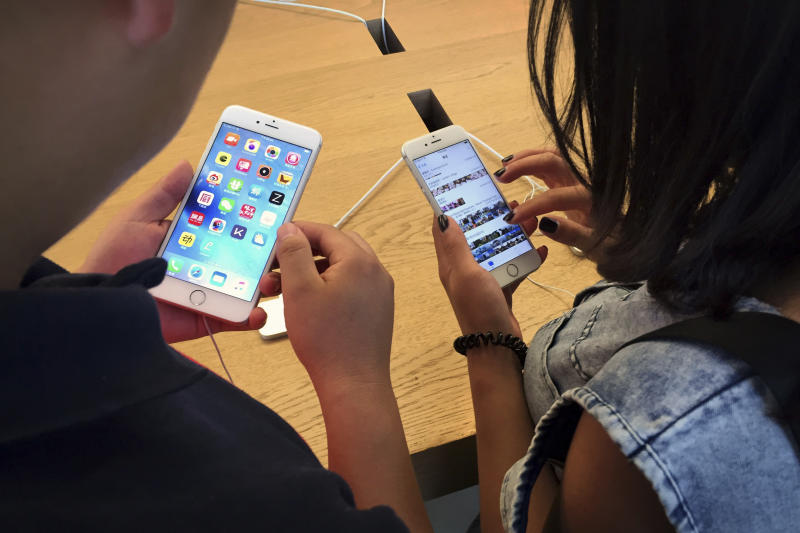 FILE - In this Saturday, June 18, 2016, file photo, customers try out Apple iPhone 6s models on display at an Apple Store in Beijing. New documents from WikiLeaks, posted Thursday, March 23, 2017, point to an apparent CIA program to hack Apple's iPhones and Mac computers such that the exploits persist even after the devices are reset to factory conditions. Apple says the purported hacking techniques have all been fixed in recent iPhones and Mac computers. (AP Photo/Mark Schiefelbein, File)