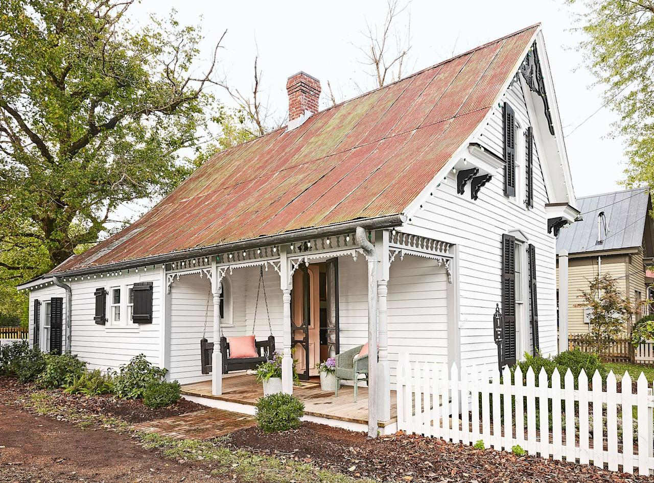 <p>A refurbished cottage gets an extra dose of charm thanks to the white picket fence that encloses the side yard. </p>