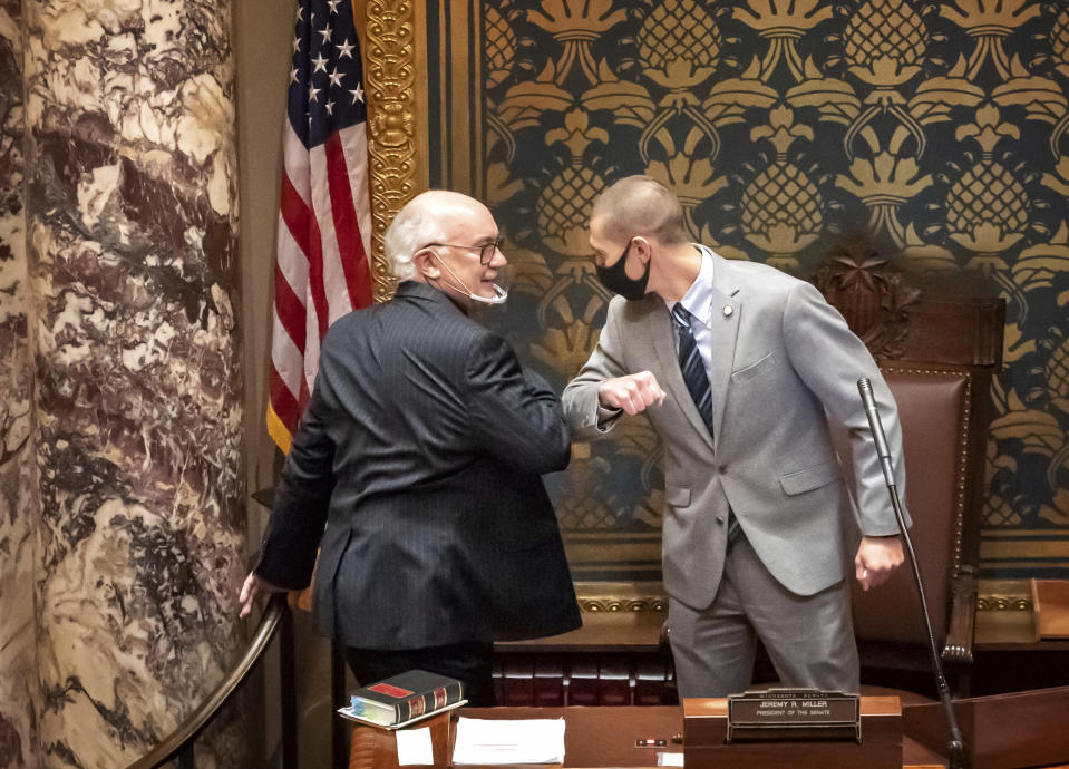 FILE - In this Nov. 12, 2020 file photo, outgoing Minnesota State Senate President Senate President Jeremy Miller, R-Winona gave Sen. David Tomassoni, DFL-Chisholm a congratulatory elbow bump before Tomassoni addressed the Senate Chamber in St. Paul, Minn. At least 187 state legislators nationwide have tested positive for the virus and four have died since the pandemic began, according to figures compiled by The Associated Press. Twelve Arkansas lawmakers have tested positive for the virus over the past month, the second largest known outbreak in a state legislature. (Glen Stubbe/Star Tribune via AP)