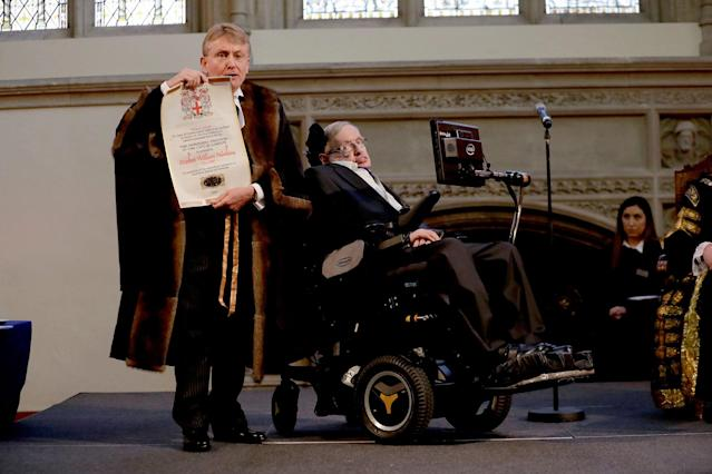 <p>Britain's Professor Stephen Hawking is presented with his illuminated Freedom scroll by the Chamberlain of the City of London Peter Kane as he receives the Honorary Freedom of the City of London during a ceremony at the Guildhall in the City of London, March 6, 2017. (Photo: Matt Dunham/AP) </p>
