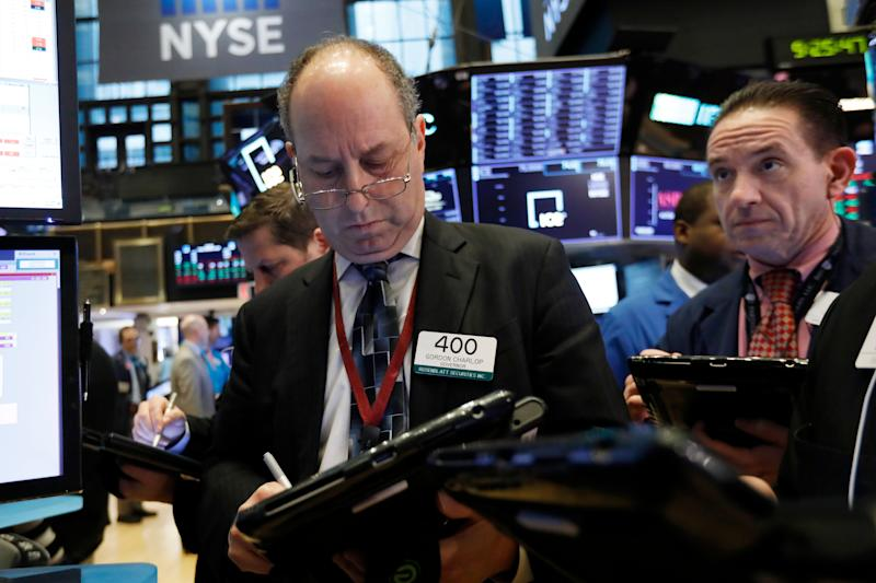 Traders Gordon Charlop, left, and Tommy Kalikas work on the floor of the New York Stock Exchange, Friday, Feb. 8, 2019. Stocks are opening lower on Wall Street as a mixed bag of earnings reports didn't inspire investors to get back to buying stocks. (AP Photo/Richard Drew)
