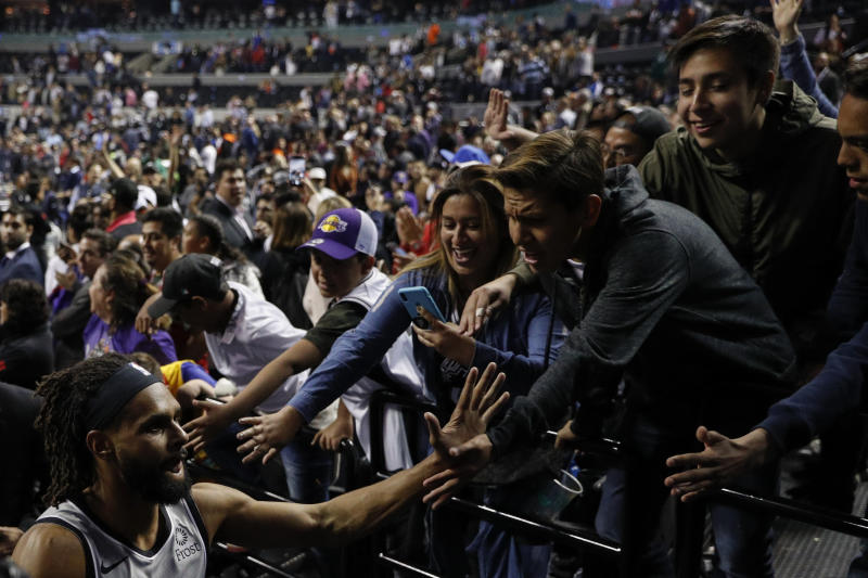 San Antonio Spurs' Patty Mills is greeted by fans as he jogs out of the arena following the Spurs regular-season NBA basketball game against the Phoenix Suns in Mexico City, Saturday, Dec. 14, 2019. Patty Mills made a jumper from the free throw line with 0.3 seconds left and the San Antonio Spurs outlasted the Phoenix Suns 121-119 in overtime Saturday.(AP Photo/Rebecca Blackwell)
