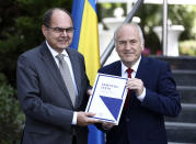 Christian Schmidt, new head of Bosnia's Office of the High Representative, or OHR, left, poses with Valentin Inzko, the outgoing head of OHR, during a ceremony in the capital Sarajevo, Bosnia, Monday, Aug. 2, 2021. Schmidt on Monday took office as the top international official in Bosnia, amid tensions with the country's Serbs who have rejected both his appointment and a ban on genocide denial brought by his predecessor. (AP Photo)