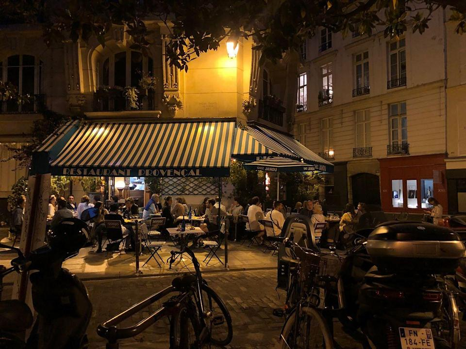 """<p><a href=""""https://www.chezjanou.com"""" rel=""""nofollow noopener"""" target=""""_blank"""" data-ylk=""""slk:Chez Janou"""" class=""""link rapid-noclick-resp"""">Chez Janou</a> is a much loved and very chic bistro around the corner from the Marais's picturesque Place des Vosges. I've always gone to Chez Janou for its liveliness and location, as well as for the food, especially the great <em>mousse au chocolat</em>, which comes in a vast terrine and is doled out generously at your table. But this time, I was struck by a new freshness to the old classics. The richness of the <em>magret de canard </em>was cut with fresh rosemary; the <em>gambas flambées au Pastis</em> was accompanied by anise-scented basmati; and the <em>crème brulée</em> carried notes of orange blossom. </p>"""