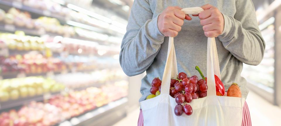 A woman holding a reusable grocery shopping bag in a supermarket. (PHOTO: Getty)