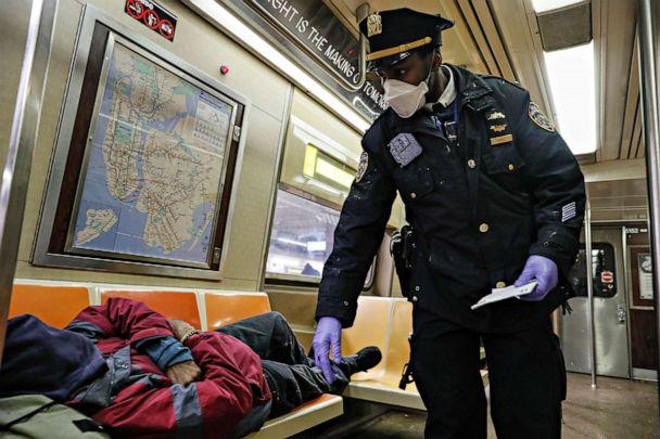 PHOTO: NYPD officers wake up sleeping passengers and direct them to the exits at the 207th Street A-train station, April 30, 2020, in the Manhattan borough of New York. (John Minchillo/AP)