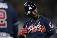 Atlanta Braves' Ozzie Albies takes a moment to clear dirt from his eyes after reaching first base on a wild pitch during the sixth inning of a baseball game against the San Diego Padres, Friday, Sept. 24, 2021, in San Diego. (AP Photo/Gregory Bull)