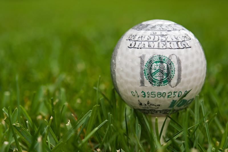 A golf ball with the markings of a hundred dollar bill on a tee in the grass.