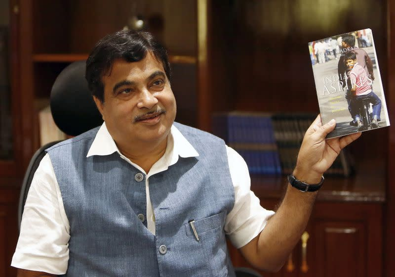 India's Transport and Shipping Minister Gadkari displays a book written by him at his office in New Delhi