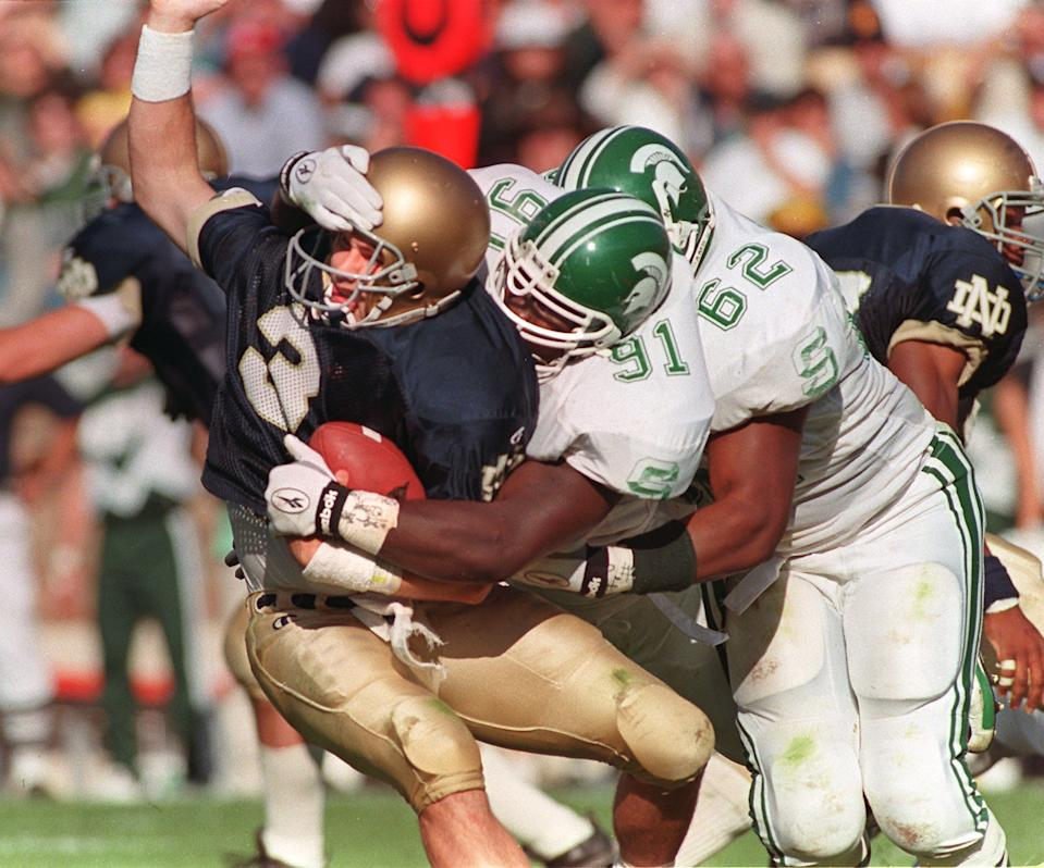 MSU defenders Robaire Smith (91) and Robert Newkirk (62) sack Notre Dame quarterback Ron Powlus on Sat. 9/20/97.