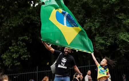 Supporters of Jair Bolsonaro, far-right lawmaker and presidential candidate of the Social Liberal Party (PSL), hold up the Brazilian flag during a demonstration in Sao Paulo, Brazil, October 21, 2018. REUTERS/Nacho Doce