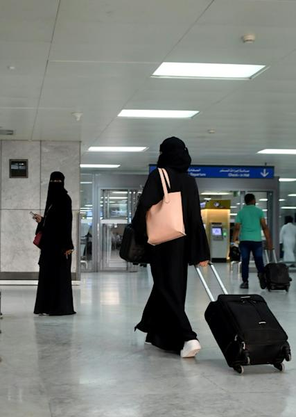 A Saudi woman rolls her suitcase at the departure hall of the Jeddah Airport (AFP Photo/-)