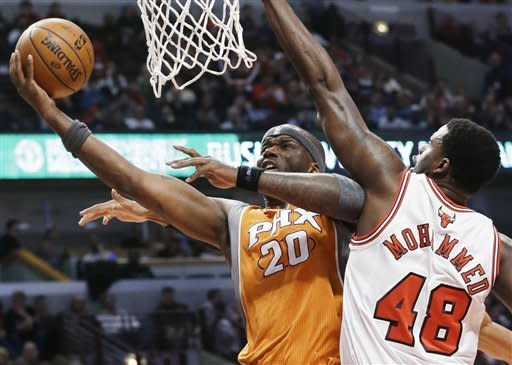 Phoenix Suns center Jermaine O'Neal, left, drives to the basket against Chicago Bulls center Nazr Mohammed during the first half of an NBA basketball game in Chicago on Saturday, Jan. 12, 2013. (AP Photo/Nam Y. Huh)