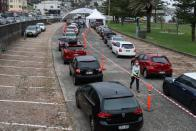 Vehicles queue as medical personnel administer tests at a drive-through COVID-19 testing centre in Sydney