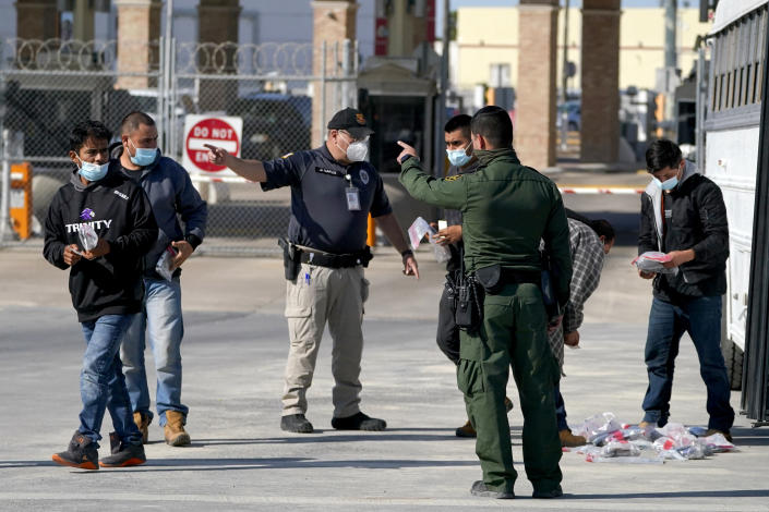 """U.S. Customs and Border Protection officers, center, instruct migrants to walk toward the McAllen-Hidalgo International Bridge while deporting them to Mexico, Saturday, March 20, 2021, in Hidalgo, Texas. The fate of thousands of migrant families who have recently arrived at the Mexico border is being decided by a mysterious new system under President Joe Biden. U.S. authorities are releasing migrants with """"acute vulnerabilities"""" and allowing them to pursue asylum. But it's not clear why some are considered vulnerable and not others. (AP Photo/Julio Cortez)"""
