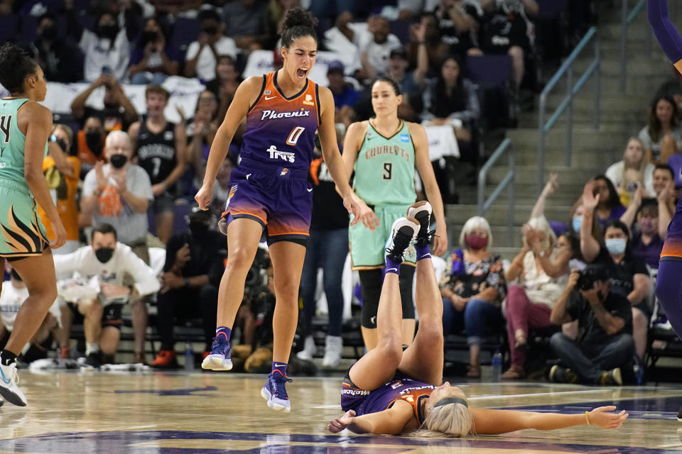 Phoenix Mercury guard Kia Nurse (0) celebrates with guard Sophie Cunningham (9) in front of New York Liberty guard Rebecca Allen (9) during the second half in the first round of the WNBA basketball playoffs, Thursday, Sept. 23, 2021, in Phoenix. Phoenix won 83-82. (AP Photo/Rick Scuteri)