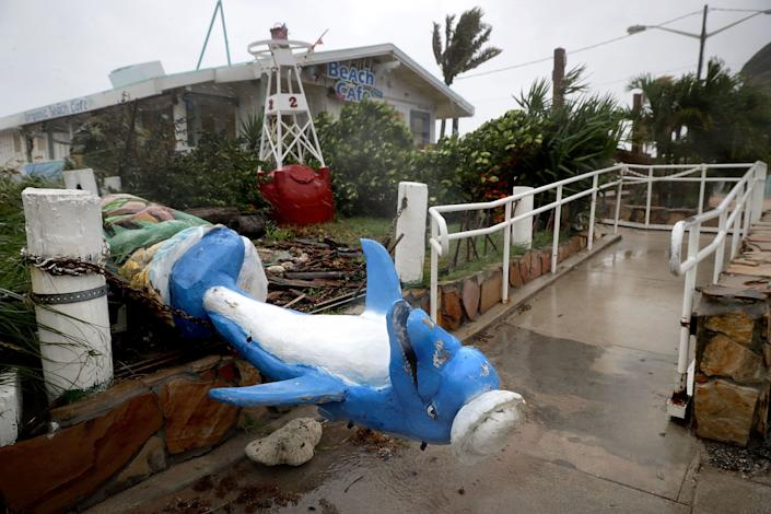 A dolphin statue at Anglin's Fishing Pier lies toppled by Hurricane Irma.