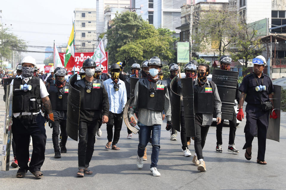 Anti-coup protesters march with makeshift shields during a demonstration in Mandalay, Myanmar, Friday, March 12, 2021. Myanmar's security forces shot to death at least 10 people protesting the military's coup, spurning a U.N. Security Council appeal to stop using lethal force. (AP Photo)